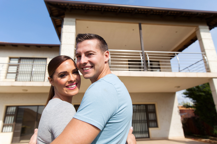 couple looking back in front of their house